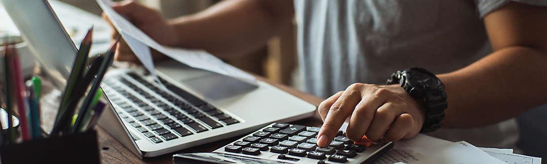 A man at his computer going through bills.