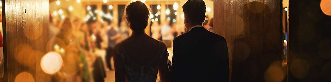 Newly married couple entering a reception hall.