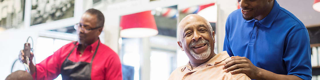 Two men taking care of customers in a barbershop.