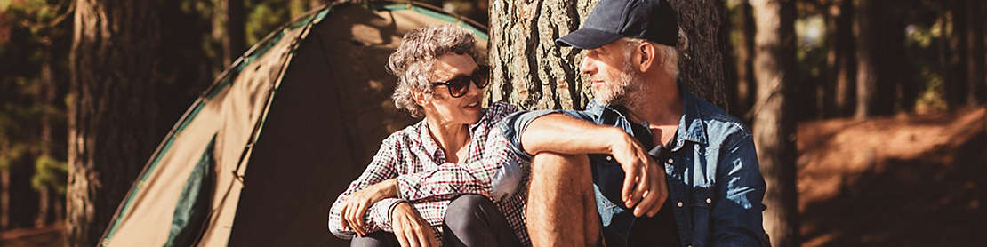 A mature couple sitting under a tree outside a camping tent.