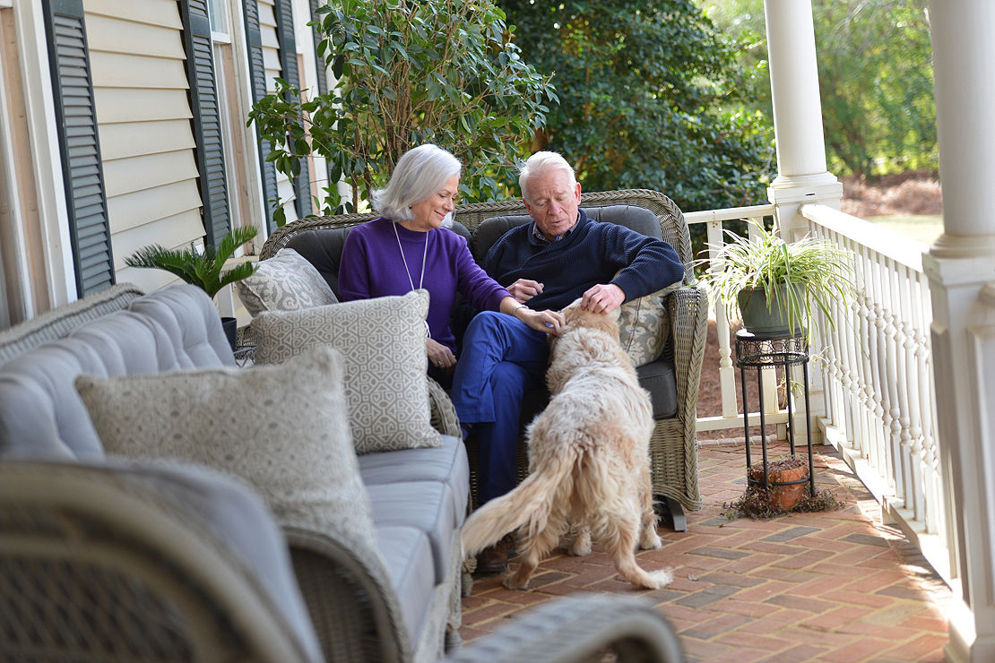 Jill Tigner and Mike Venable sitting on their porch playing with their dog.