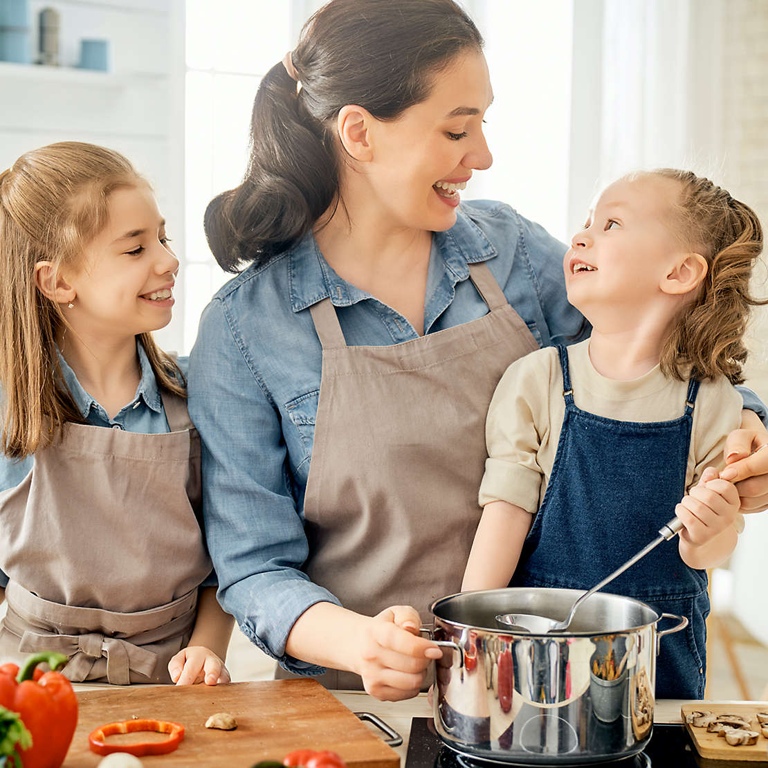 Mother and children cook pasta in the kitchen