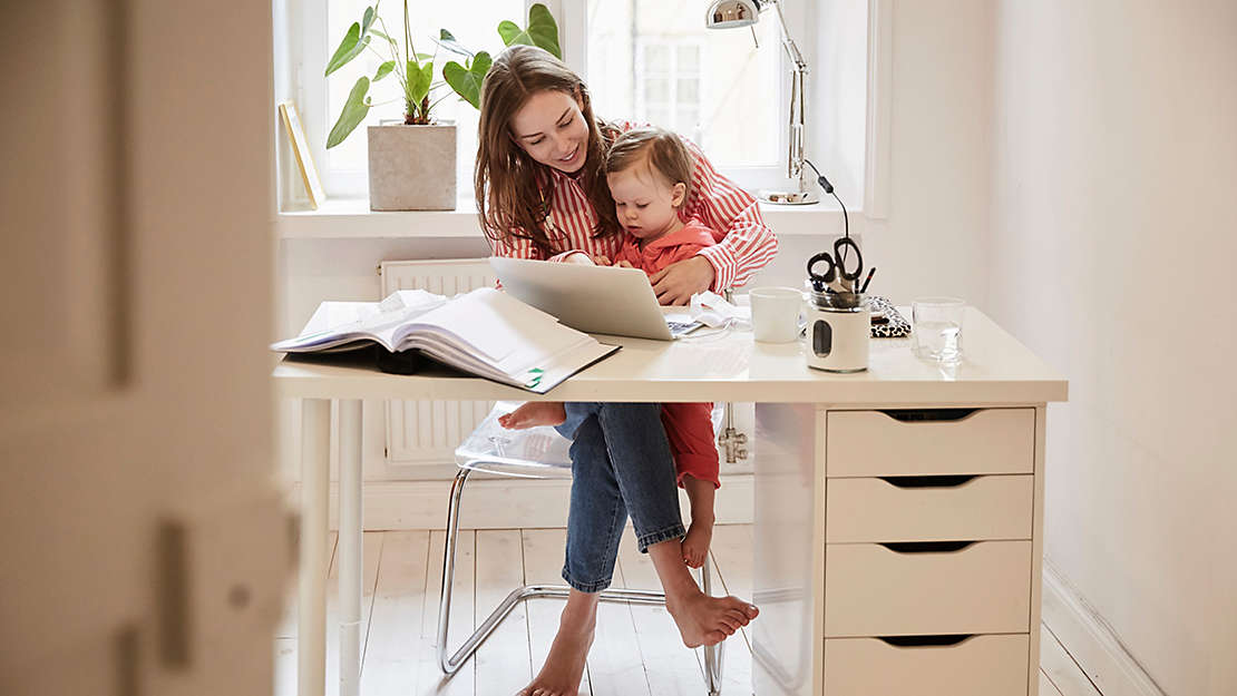 Woman working at desk with child