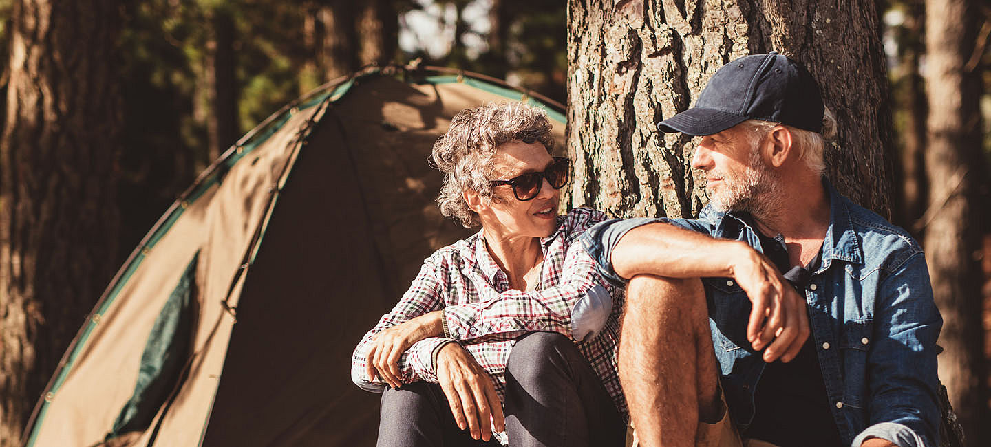 Older couple camping in the woods.