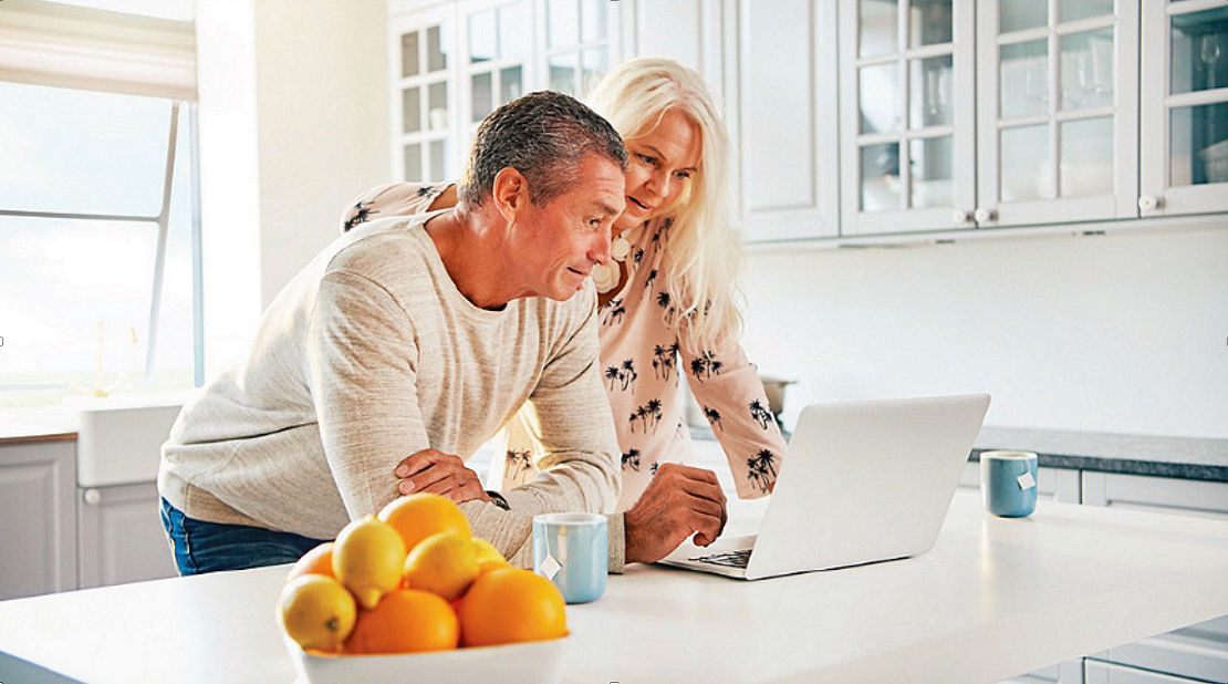 Couple looking at Long Term care options on a laptop in their kitchen.