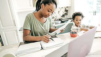 Mother doing paperwork; child in a highchair in the kitchen