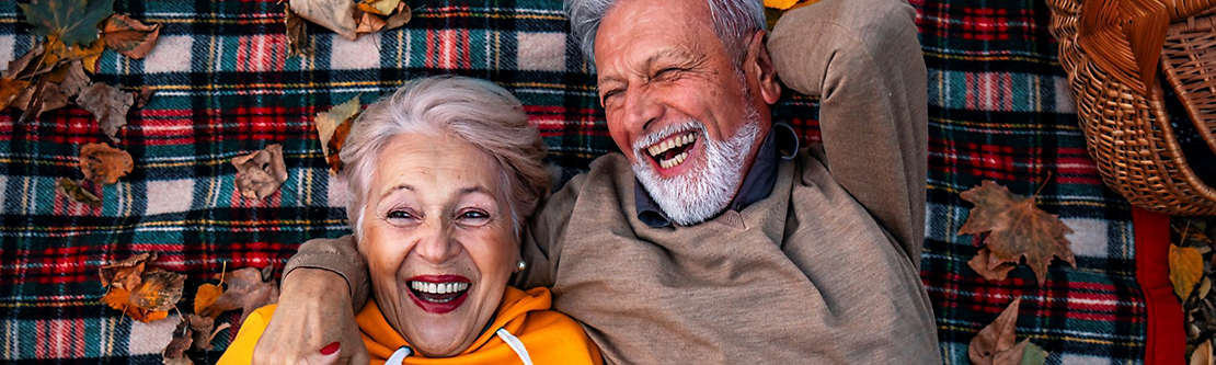 A mature couple laying on a picnic blanket laughing.