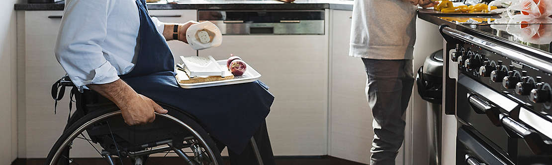 An older man in a wheelchair and a young boy preparing food in a kitchen.