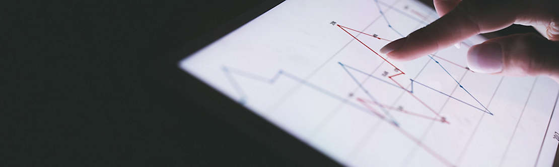 A finger pointing at a graph displayed on a tablet.
