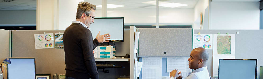 Two men talking at their cubicles at work.