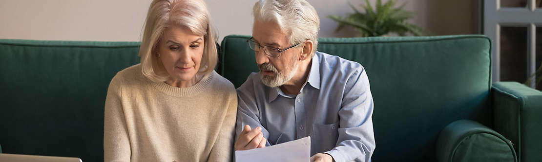 A mature couple sitting on a couch reviewing paperwork.