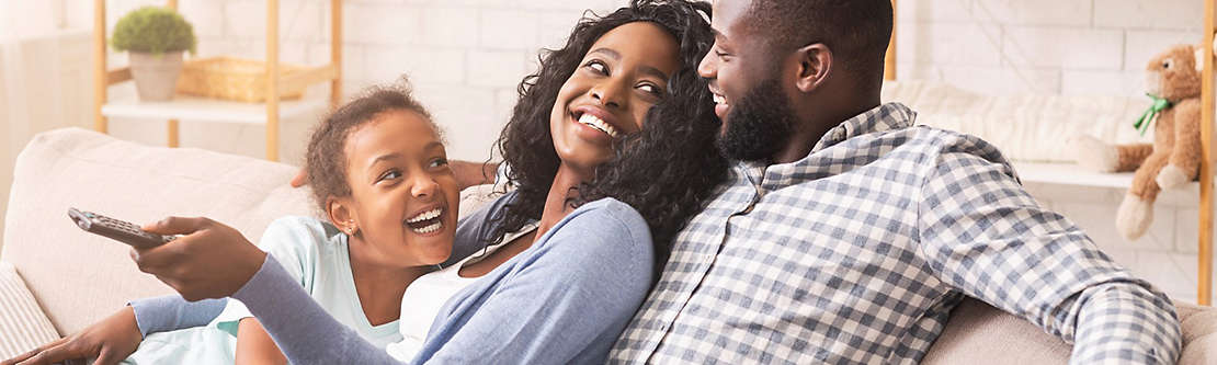 Family laughing together sitting on couch.