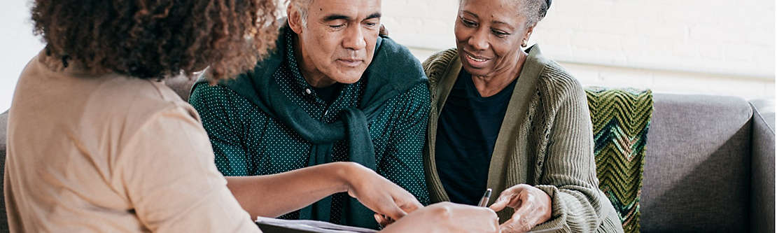 A mature couple at home reviewing paperwork with an agent.