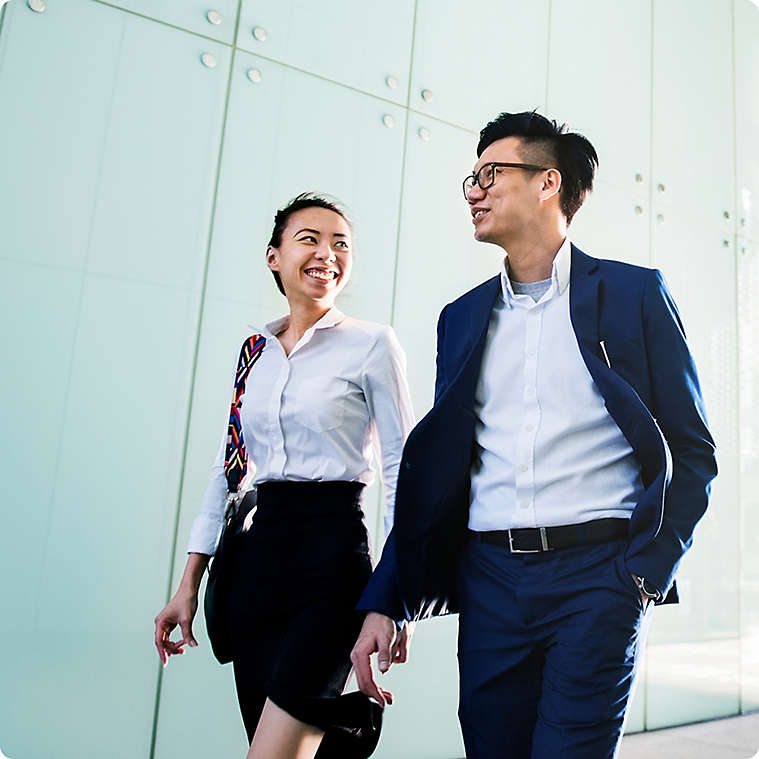 Two employees walking in professional attire