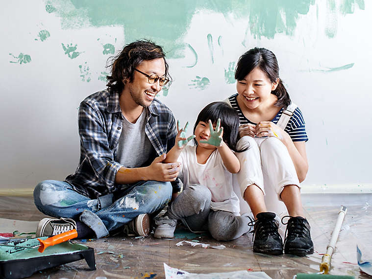 Two people painting with child