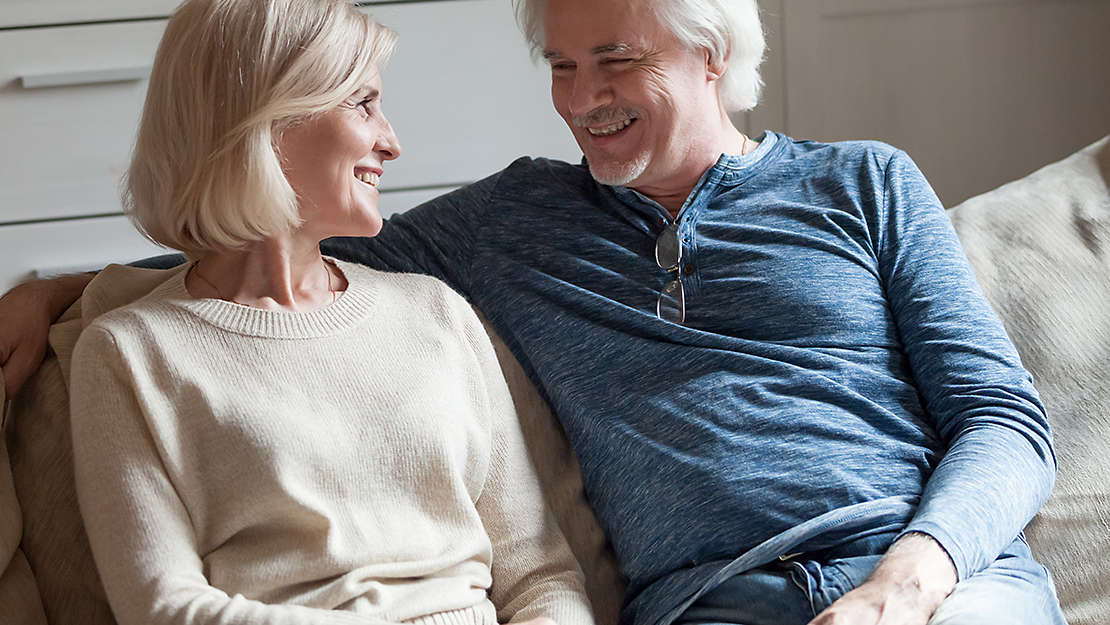Elderly couple on couch smiling