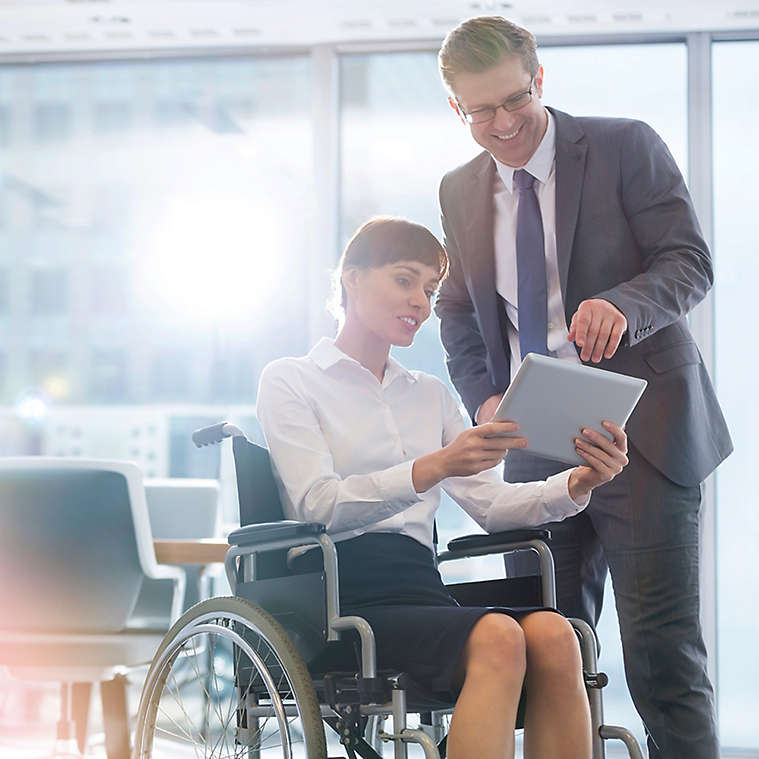 Woman in wheelchair showing a man a document on a tablet.