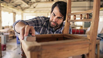Man making a chair in a wood shop.