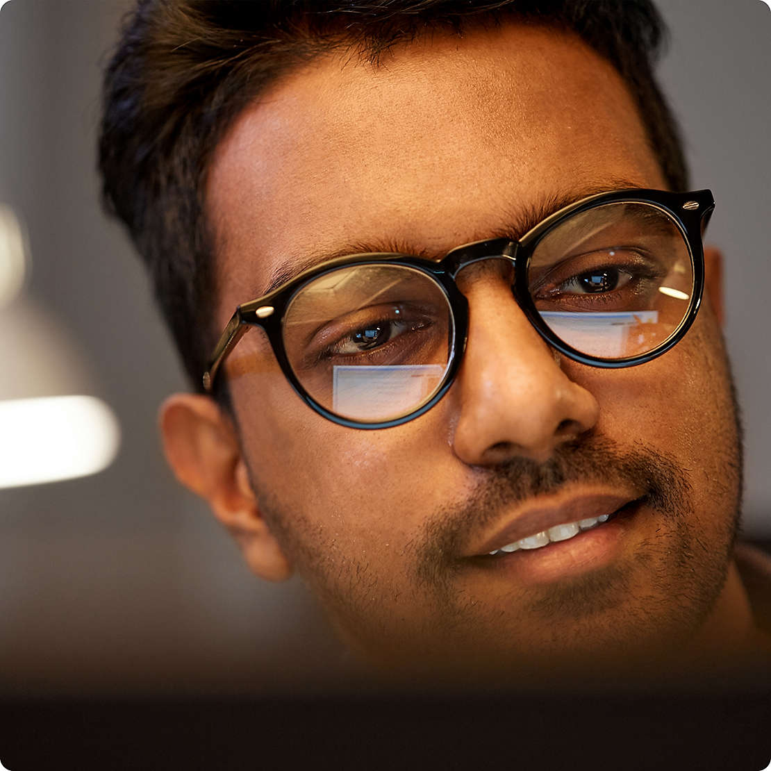 Man staring at computer screen with glasses on