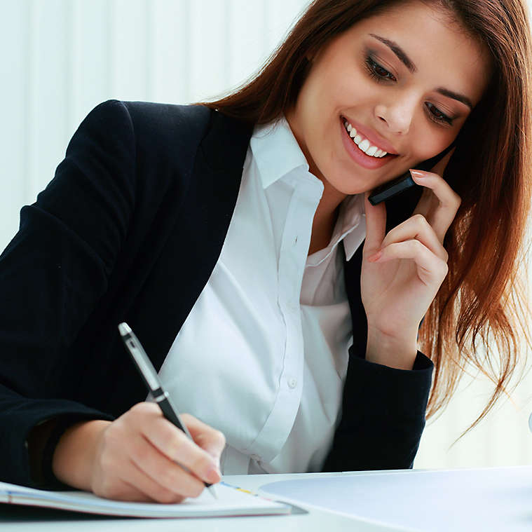 Person on the phone while writing in notebook.