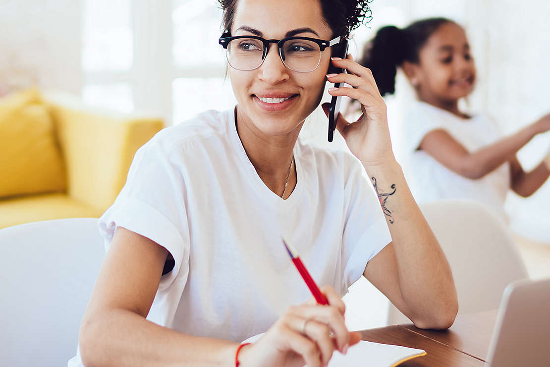 Woman on the phone while taking notes and working on laptop