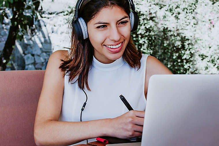 Woman smiling and taking notes while listening to a video on her laptop.