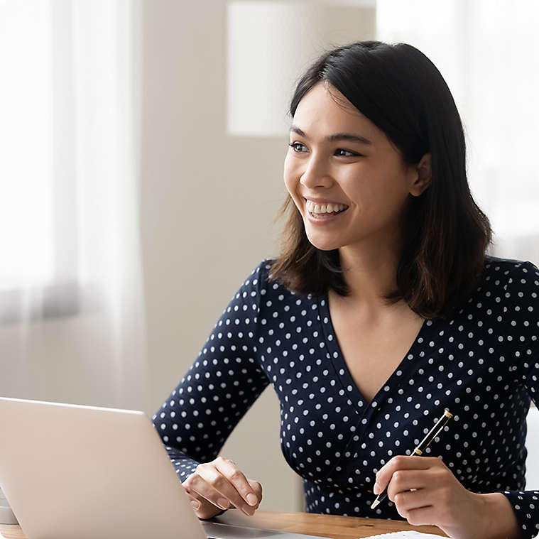 Financial professional smiling with laptop and pen