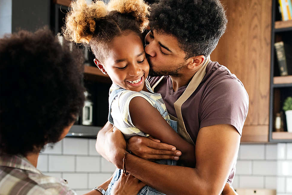 Father holding and kissing his young daughter in the kitchen.