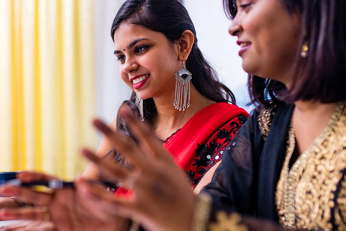 South Asian mother and daughter talking at the table