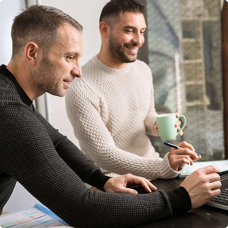 LGBTQ couple planning and using a computer