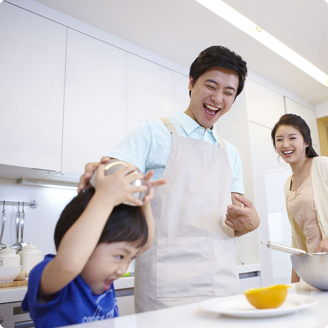 Korean family cooking in kitchen with young son