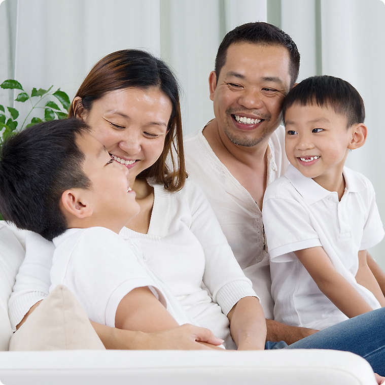 Vietnamese family smiling and sitting with two young sons