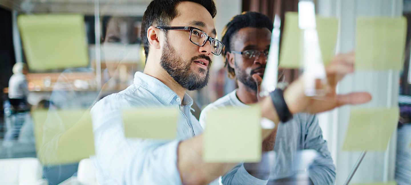 Two employees looking at sticky notes on whiteboard