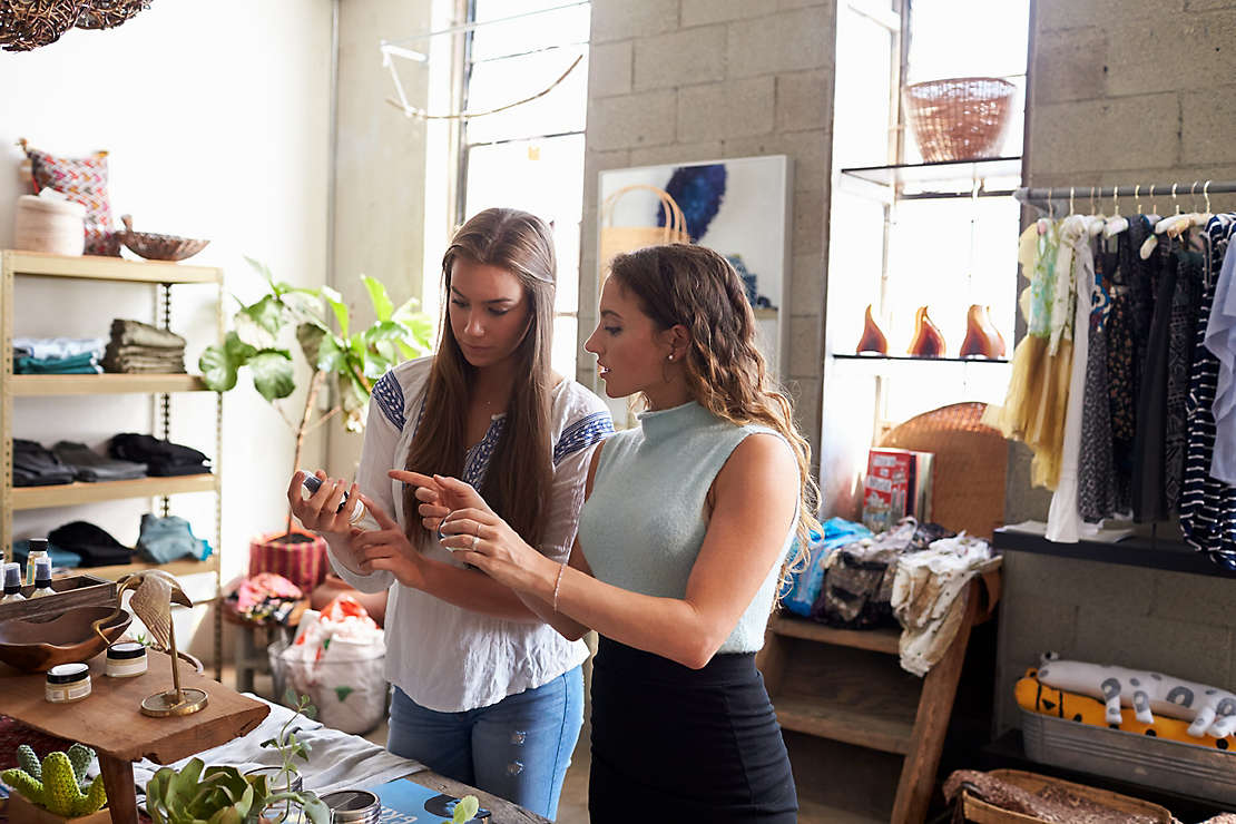 Two women looking at object in a store
