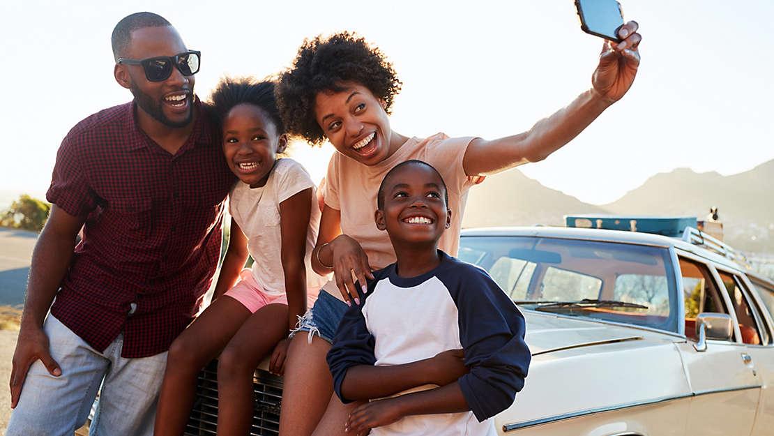 Family taking photo on car