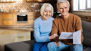 Happy relationships. Joyful positive elderly couple sitting together and smiling while checking the bills