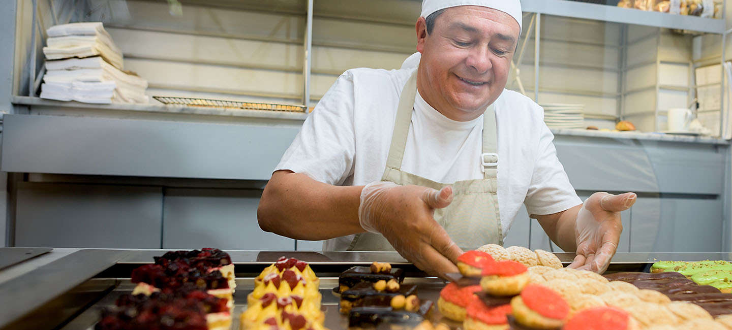 Baker working at the front counter of a bakery.