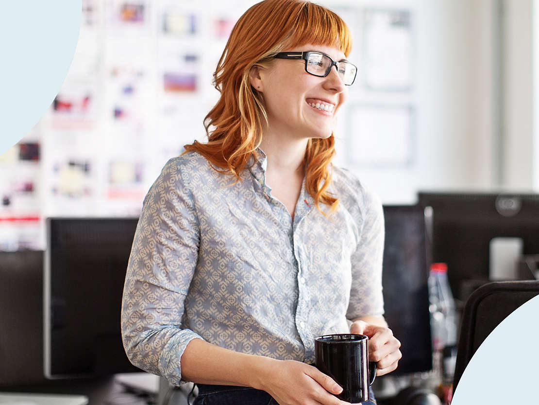 Smiling financial professional in glasses with coffee