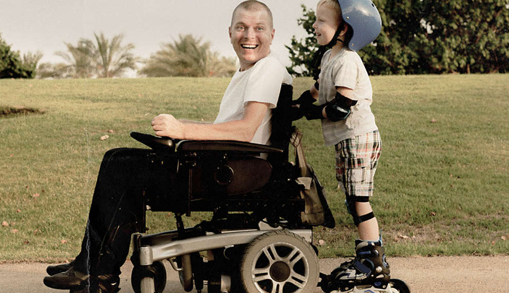 Man in wheel chair getting pushed by son in roller blades.