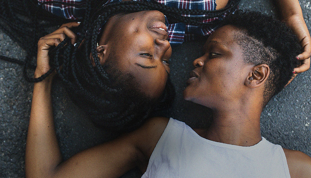 Two women laying on the ground looking at each other.
