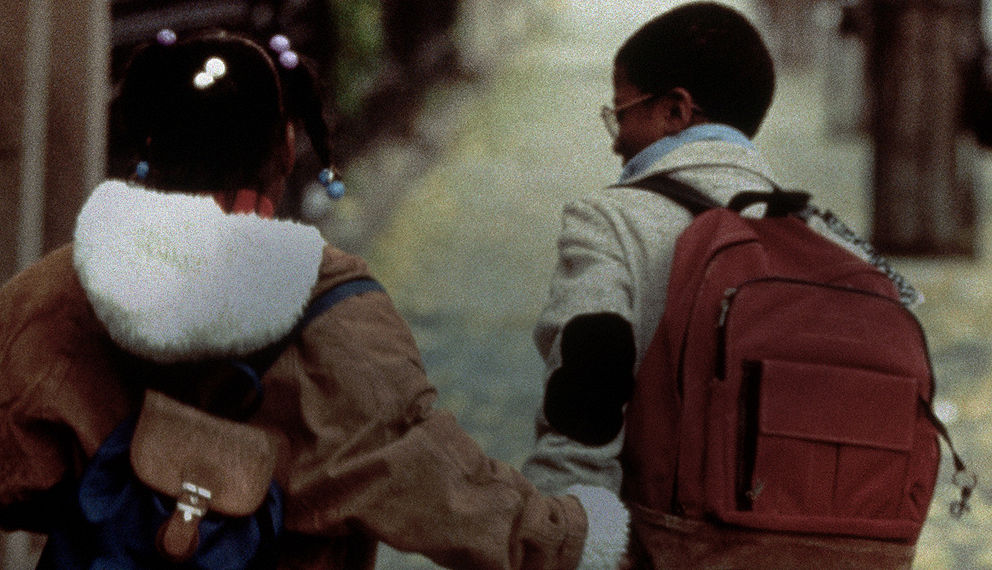 Two young children holding hands walking down the street together.