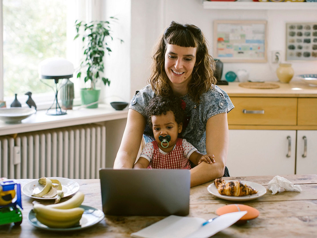 Woman and baby working in the kitchen with a laptop.