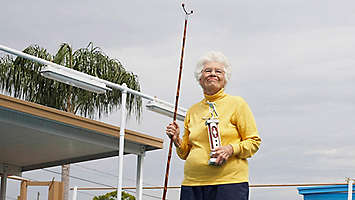 Older women outside holding shuffle board stick and trophy